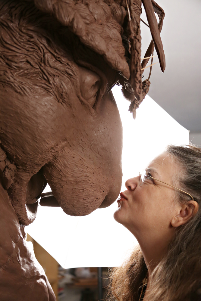 Texas artist kisses the nose of a clay sculpture