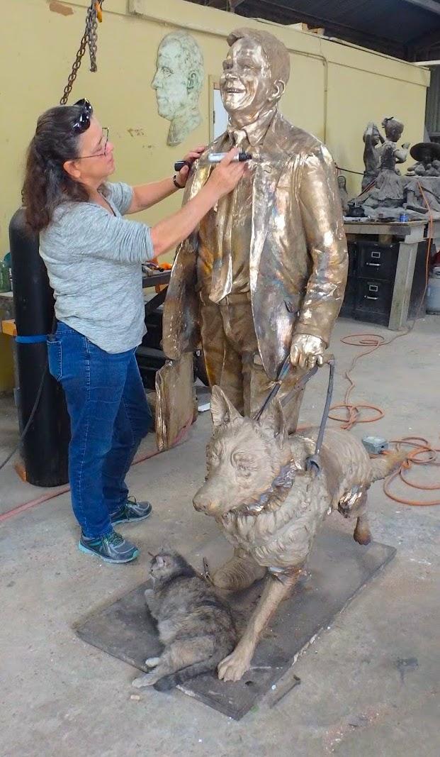 Sculptor Bridgette Mongeon looks over the metal of a bronze statue