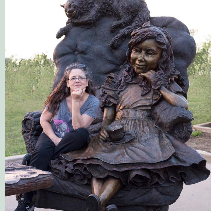 Bridgette Mongeon Sits in the bronze chair with Alice in Wonderland In Texas